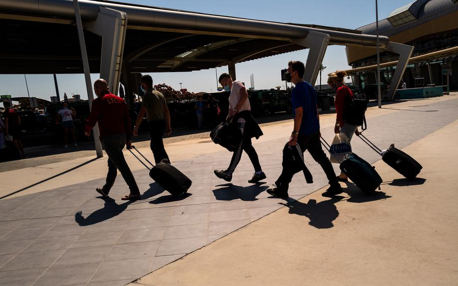 Tourists wheel luggage from the arrivals terminal at Faro Airport in Faro, Portugal, on May 29, 2021.