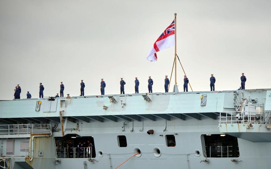 Royal Navy sailors man the rails of the HMS Queen Elizabeth as the aircraft carrier arrives at Yokosuka Naval Base, Japan, Saturday, Sept. 4, 2021.