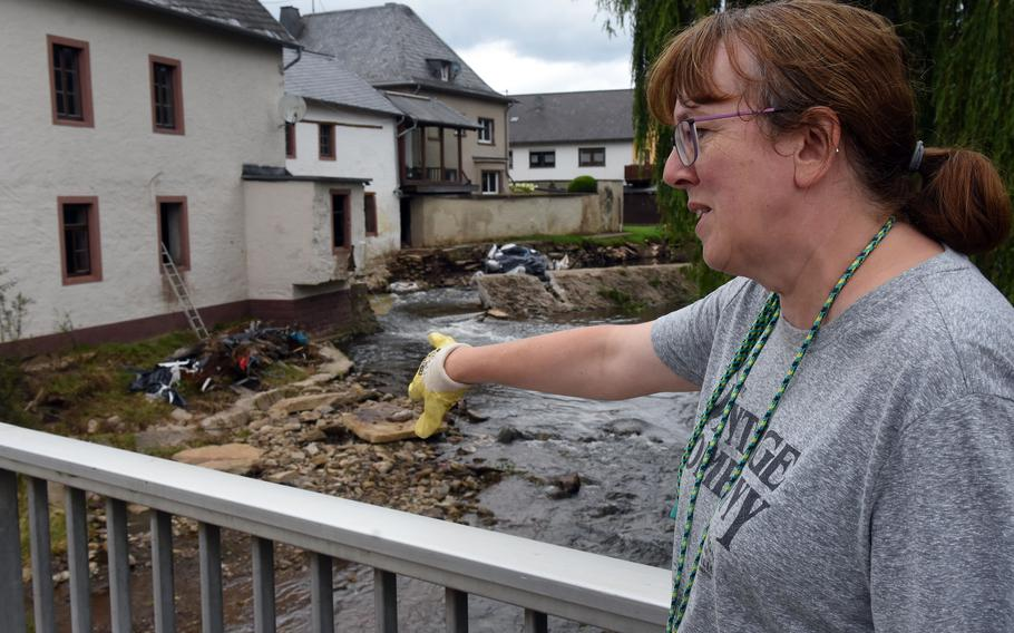 Doris, a resident of Rittersdorf, Germany, who declined to provide her last name, stands on a bridge overlooking her familys mill and a house her family rents to Americans on the banks of the Nims River, July 31, 2021. Both buildings were damaged during historic floods last month. Doris said the river at its peak covered the bridge on which she was standing.