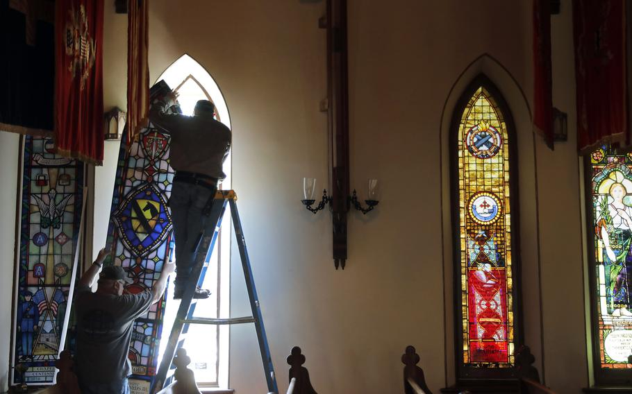 Jeff Speake, left, and Troy Kidd of Lynchburg Stained Glass install a temporary window on the Chapel of the Centurion on Fort Monroe on June 15, 2021. Eight stained glass windows of the chapel are being removed and restored as part of a wide scale project to overhaul the oldest continually used wooden military house of worship that opened in 1856.