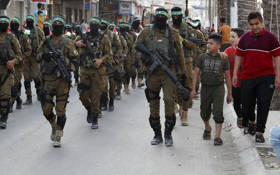 """Children talk with masked militants from the Izzedine al-Qassam Brigades, a military wing of Hamas, hold their national flags while marching along the streets of Nusseirat refugee camp, central Gaza Strip, on May 28, 2021. Arabic on the headband reads """"No God but Allah and Muhammed is his messenger, al-Qassam Brigades."""""""