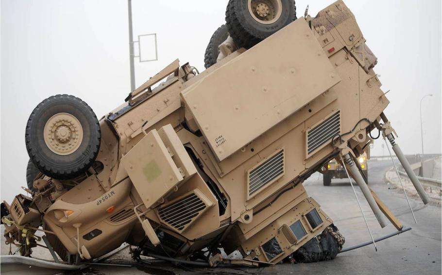 A Mine-Resistant Ambush-Protected vehicle rests on its turret and hood after a rollover. Soldiers can avoid tactical vehicle accidents by engaging and reinforcing drivers' skills training by conducting rollover drills, making sure all crew members use restraints, ensuring that tire pressure is correct on their vehicles, employing composite risk management, and briefing road conditions before each mission.