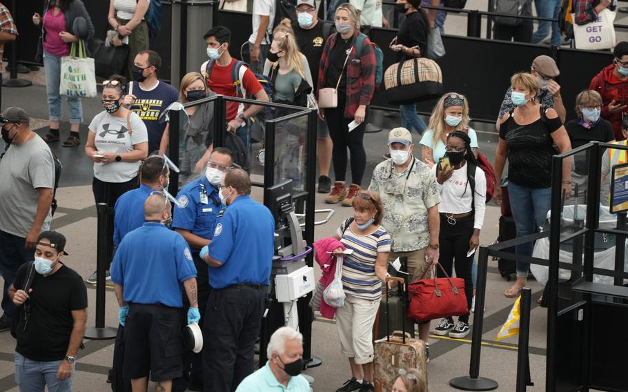 Travelers wear face coverings in the line for the south north security checkpoint in the main terminal of Denver International Airport Tuesday, Aug. 24, 2021, in Denver.