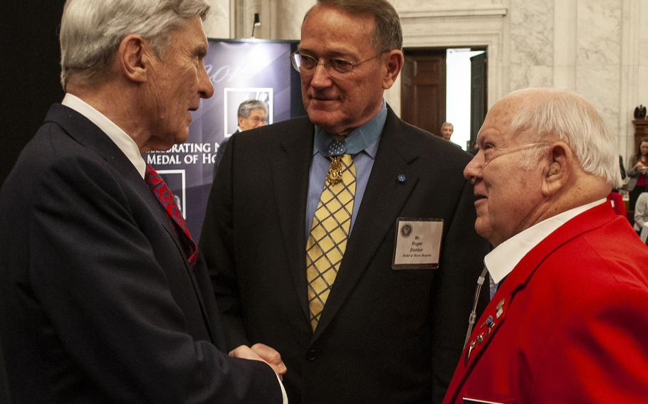 Former Sen. John Warner, left, talks with Medal of Honor recipients Roger Donlon, center, and Jack Lucas during a reception in Washington, D.C. in 2007.