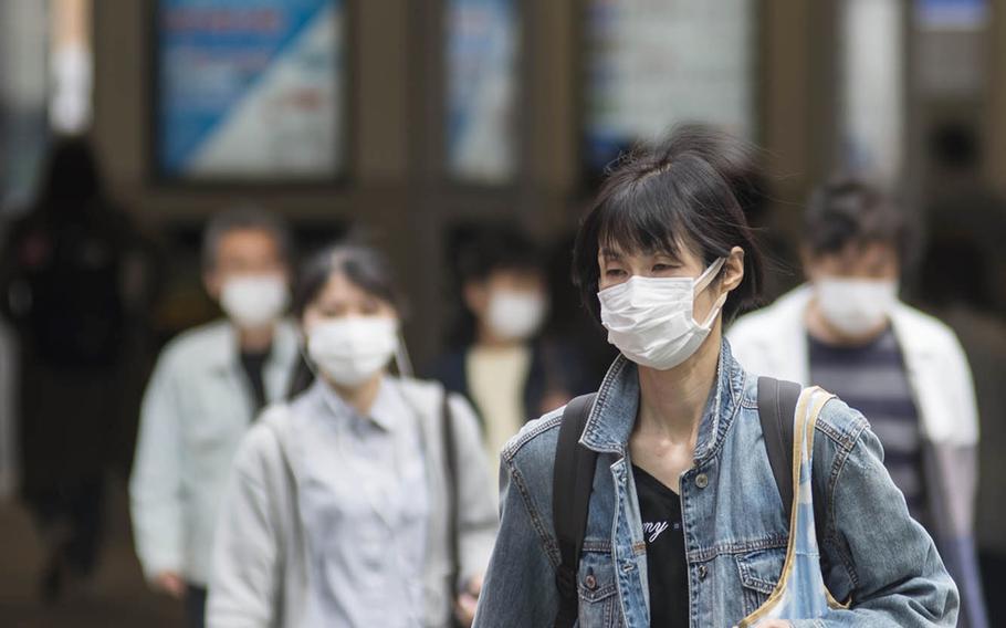 People walking near Tsunashima Station wear masks to prevent coronavirus infection earlier this spring in Yokohama, Japan.