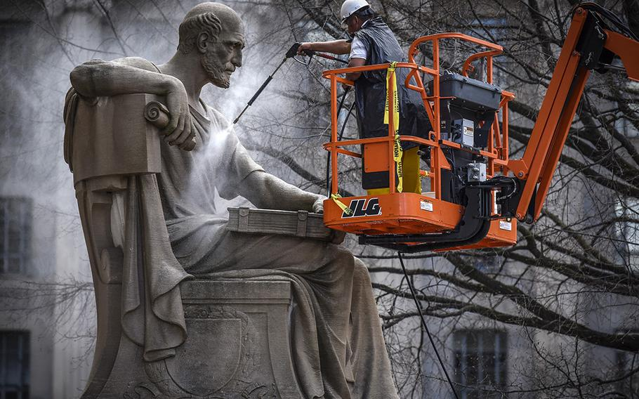 Contractors give a spring cleaning to Robert Aitken's statue from 1935 of Socrates, located on the Pennsylvania Avenue side of the National Archives in Washington, on April 4, 2017.