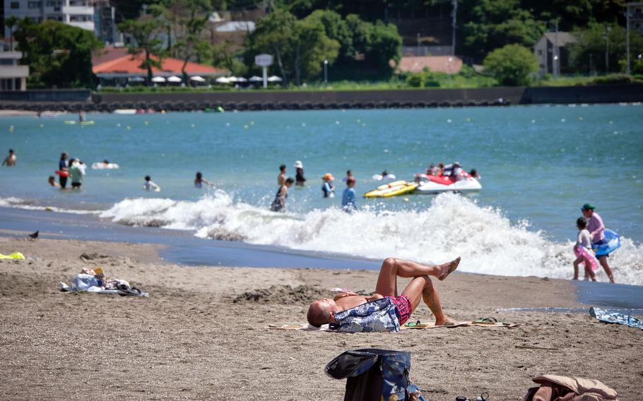 Beachgoers play and relax at Zushi Beach in Kanagawa prefecture, Japan, Tuesday, Aug. 3, 2021.