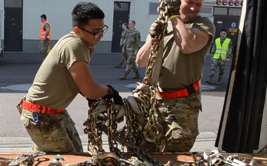 Senior Airman Gerald Dinio, left, and Airman 1st Class Matthew Lagrange of the 726th Air Maintenance Squadron out of Spangdahlem Air Base, lift chains onto a cart during the 721st Aerial Port Squadron Multi-Capable Airmen Rodeo at Ramstein Air Base on July 23, 2021.
