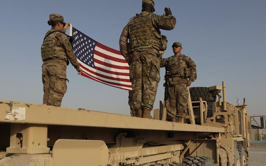 Spc. Manuel Leiva, right, with the 3rd Division Sustainment Brigade, raises his right hand and recites the oath of enlistment administered by Chaplain (Cpt.) Philibert Meyor, during a ceremony at Erbil, Iraq, Aug. 12, 2021. The Army is reducing soldiers' reenlistment window from 15 months before the end of the contract to 12 months.