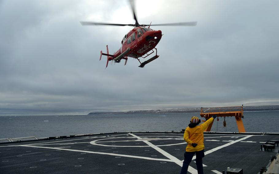 """Lt. j.g. Ainsley Fruhwirth directs a Canadian coast guard helicopter crew to take off from Healy near Resolute, Canada, on Sept. 6, 2021. The Defense Department has appointed retired Air Force Maj. Gen. Randy """"Church"""" Kee as its senior adviser for Arctic security."""