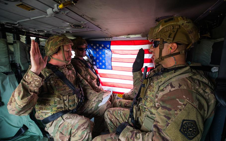 Sgt. Alex Apostolou, a maintenance noncommissioned officer with the 108th Sustainment Brigade Task Force Lincoln, Team Blackhawks, reenlisted into the U.S. Army aboard a UH-60 Black Hawk helicopter on Dec. 6, 2019, over the skies of Baghdad, Iraq. The reenlistment ceremony was administered by Chief Warrant Officer 2 Lucas Miles, S1 Officer in Charge, with the 108th Sustainment Brigade. (U.S. Army National Guard photo by Sgt. William Ploeg)