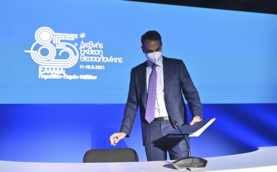Greece's Prime Minister Kyriakos Mitsotakis takes his seat for a news conference at the Thessaloniki International Fair, in the northern city of Thessaloniki, Greece, Sunday, Sept. 12, 2021.