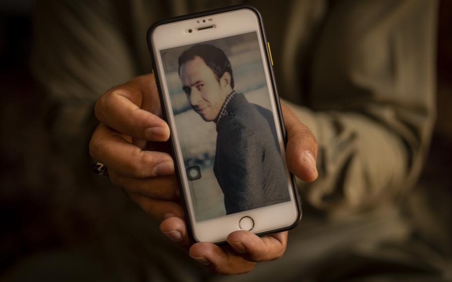 Amal Ahmadi, 32, holds a picture of his slain brother Zemerai Ahmadi at the family house in Kabul, Afghanistan, on Monday, Sept. 13, 2021.