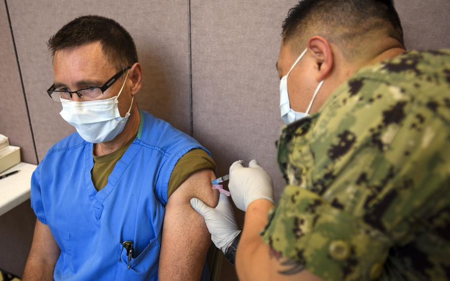 A Navy hospital corpsman administers a COVID-19 vaccine to a fellow medical worker early this year at Naval Base Guam.