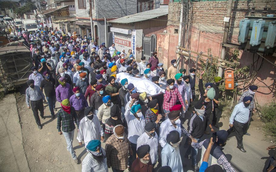 In this Oct. 8, 2021 file photo, Sikh community members carry the body of slain Satinder Kaur, a government school teacher during her funeral procession in Srinagar, India.