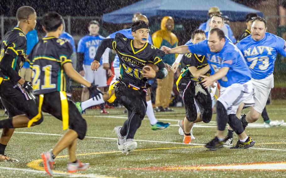 Senior Douglass Tackney, with ball, and his Robert D. Edgren teammates played flag football in the driving rain against Navy sailors at Misawa for their homecoming game.