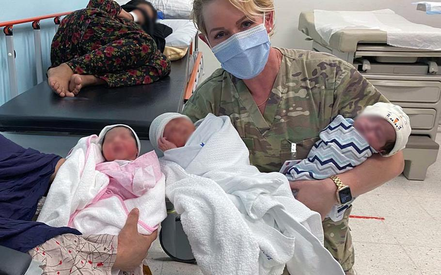 Dr. (Maj.) Elaina Wild, 379th Expeditionary Medical Group chief medical officer, with mothers and their newborn babies at Al Udeid Air Base, Qatar, Aug. 28, 2021. Since the base became the main stopover location for evacuees from Afghanistan on Aug. 14, 2021, members assigned to the unit helped deliver nine babies.