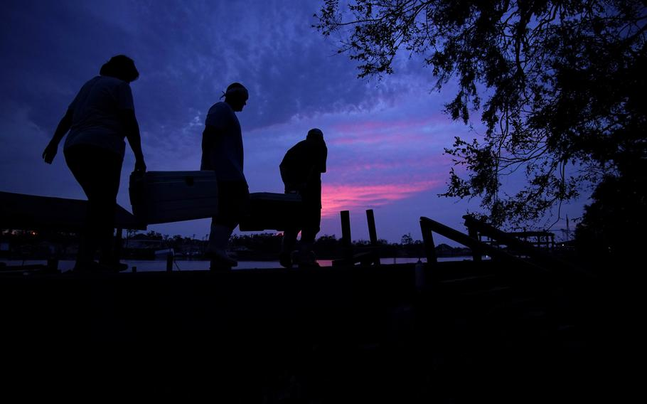 People carry supplies to their boat at dusk in the aftermath of Hurricane Ida, Wednesday, Sept. 1, 2021, in Jean Lafitte, La.
