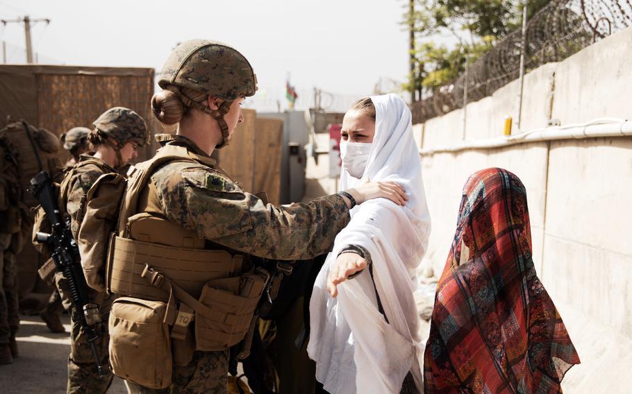 A Marine checks two civilians during processing through a checkpoint during an evacuation at Hamid Karzai International Airport, Kabul, Afghanistan, Aug. 18, 2021.