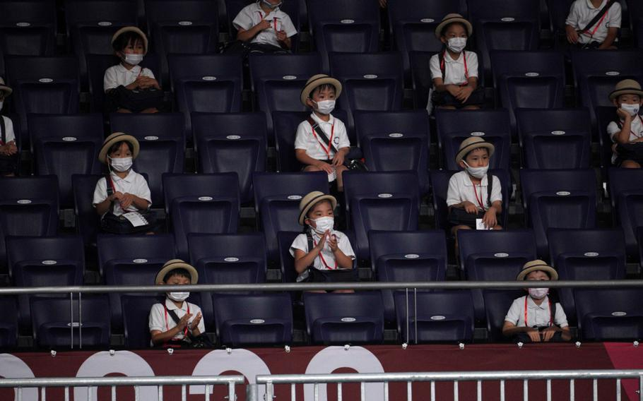 Japanese schoolchildren watch a Paralympics wheelchair rugby match between the United States and New Zealand at Yoyogi National Stadium in Tokyo, Wednesday, Aug. 25, 2021.