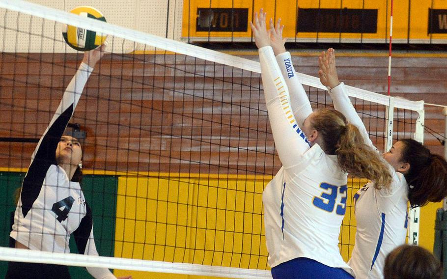 Zama's Emma Sakamoto-Flack attempts a spike against Yokota's Devynn Martin and Malia Hutchins during Saturday's Japan girls volleyball match. The Panthers won in four sets.