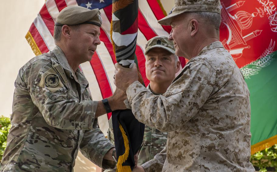Gen. Scott Miller, left, hands command of U.S. forces in Afghanistan to Marine Corps Gen. Frank McKenzie at a ceremony in Kabul, Afghanistan on Monday, July 12, 2021.