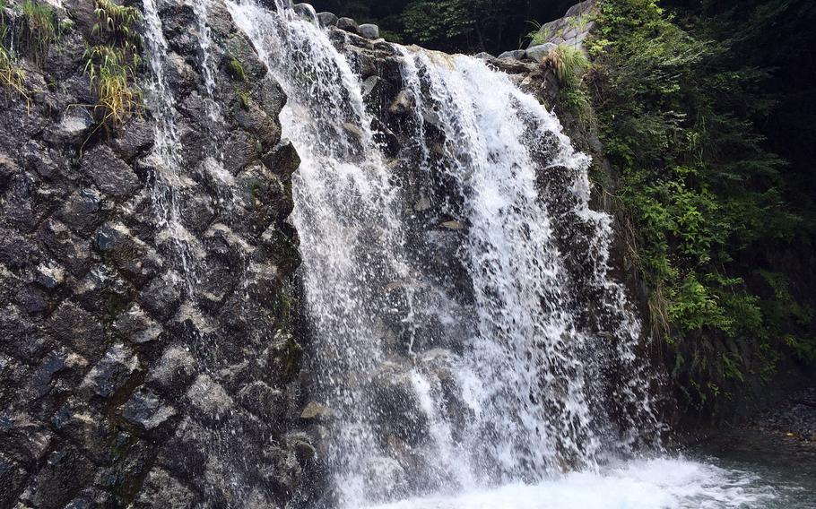 A waterfall over a dam on the river along the Tsutsuji Shindo Trail to Mount Hinokiboramaru is a summer destination of its own in Kanagawa prefecture, Japan.