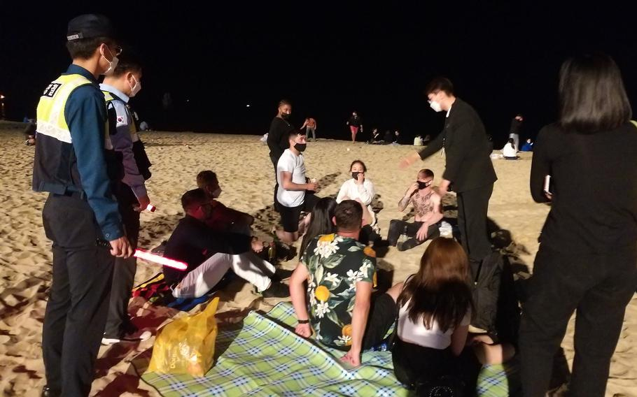 South Korean police responded to more than 30 reports of a large party involving 1,500 or more foreigners at Haeundae Beach in Busan, Saturday, May 29, 2021. Many were disregarding South Korea's coronavirus rules for wearing masks in public areas, maintaining 6 feet between individuals and limiting groups to five people.