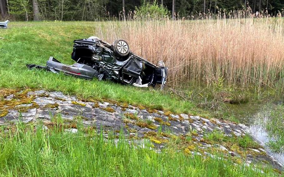 The totaled Volkswagen Jetta of a 23-year-old U.S. service member who was seriously injured in a car accident May 15, 2021, on the A9 autobahn near Bayreuth, Germany, lies on its roof near a drainage ditch.