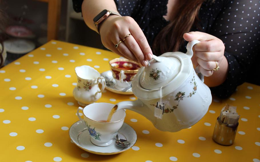 Kelly Alvarez serves a cup of breakfast tea just before our food platter arrives at Barleycorn in Mildenhall, England on May 24, 2021. Aside from English sandwiches and baked goods, the shop offers teas served in vintage china.
