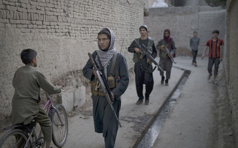 Taliban fighters patrol a neighborhood in search for a man accused in a stabbing incident, in Kabul, Afghanistan, Sunday, Sept. 12, 2021.