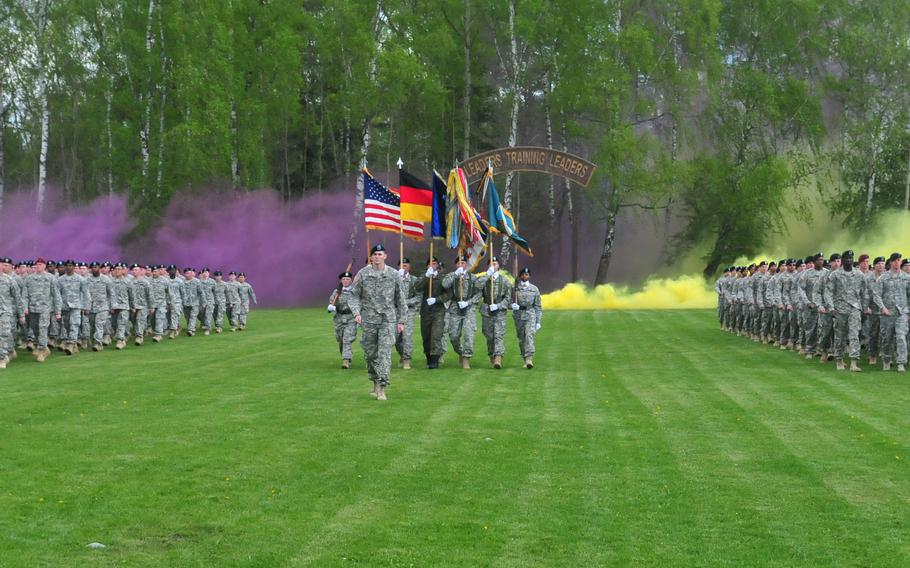 The 7th Army Noncommissioned Officer Academy's Warrior Leader Course participants march out of the wood lines through purple and yellow smoke at Camp Normandy field in in Grafenwoehr, Germany, on May 7, 2015.