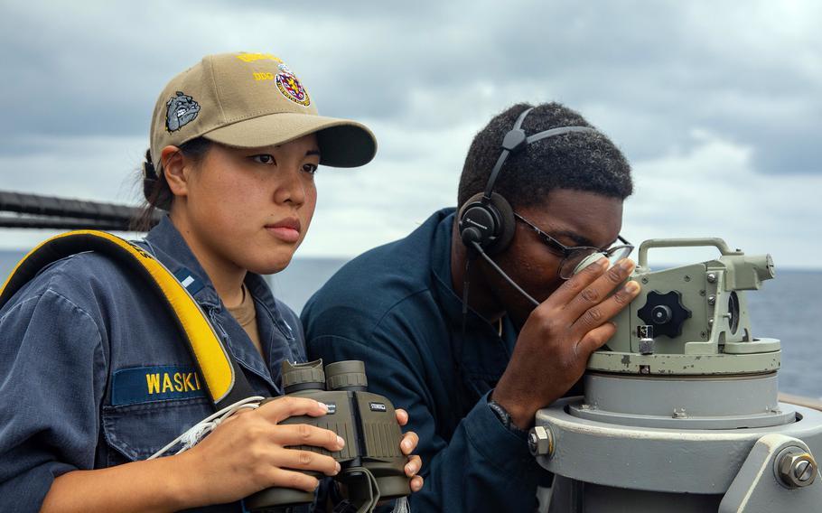 Lt. j.g. Chunchun Waskin and Seaman Samuel Figueroa Lopez scan the ocean's surface as the USS Barry passes through the Taiwan Strait, Friday, Sept. 17, 2021.