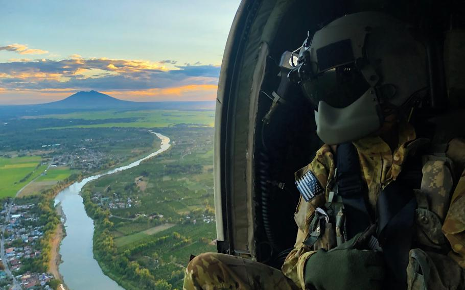U.S. Army Sgt. Kevin Sanchez, who serves as crew chief with Charlie Company, 3rd General Support Aviation Battalion, 25th Combat Aviation Brigade, studies terrain aboard a UH-60 Blackhawk aircraft as part of a flight survey during Exercise Balikatan 2019 near Mount Pinatubo, Fort Magsaysay, Philippines, April 1, 2019.
