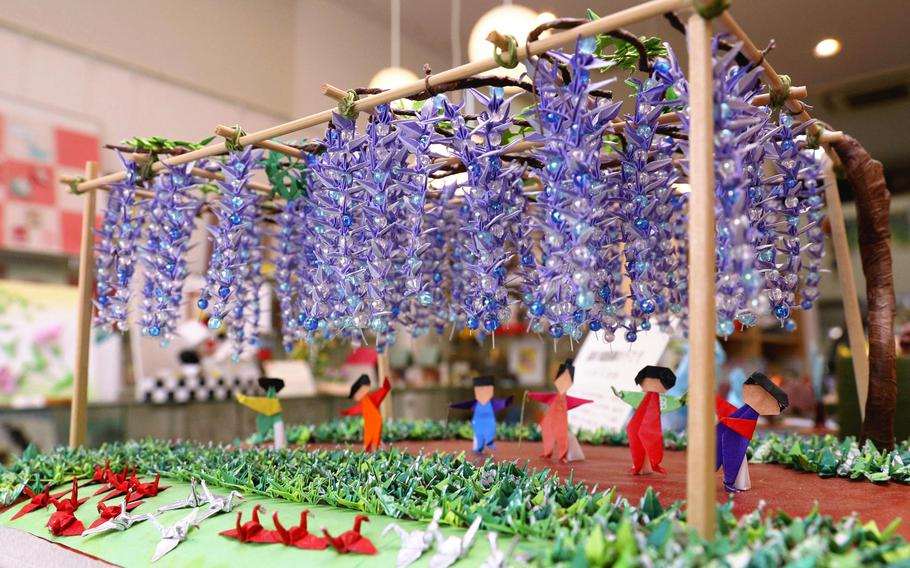 """Akira Iwabuchi's work at the Tokyo Origami Museum, """"Under the full-blown wisteria trellis of cranes!!,"""" features small origami cranes displayed in such a way to resemble a wisteria trellis and grass."""