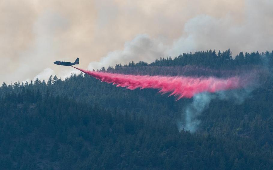 An Air National Guard C-130 out of Reno, Nev., drops fire retardant on the Beckwourth Complex Fire on July 9, 2021 near Frenchman Lake in Northern California. Military aircraft are generally asked to join firefighting efforts when all commercial air tankers are already at work or unavailable. This was one of the busiest years for military firefighting aircraft on record.
