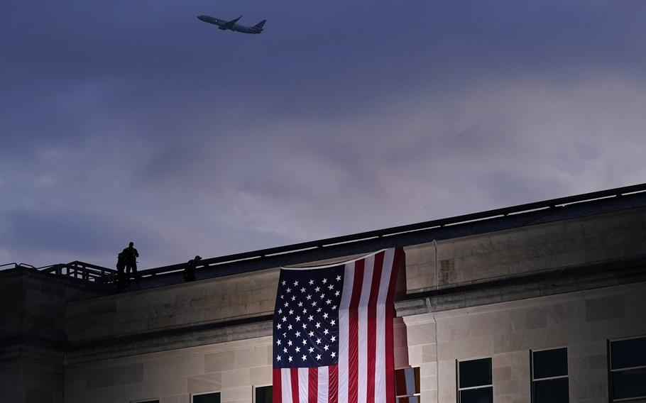 A plane takes off from Washington Reagan National Airport on Sept. 11, 2020, as a large U.S. flag is unfurled at the Pentagon ahead of ceremonies at the National 9/11 Pentagon Memorial to honor the 184 people killed in the 2001 terrorist attack on the Pentagon, in Washington.