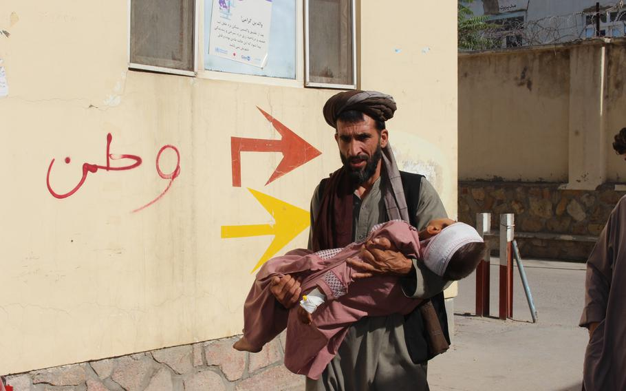 An Afghan civilian carry a wounded child to the hospital after he was injured during fighting between Taliban and government in Badghis province, northwest of Afghanistan, Wednesday, July 7, 2021.