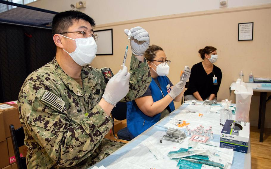 Medical workers prepare syringes with doses of the Pfizer COVID-19 vaccine this spring at Yokosuka Naval Base, Japan.