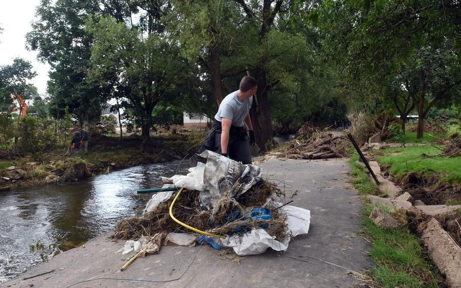 Airman Kyle Koury of Spangdahlem Air Base moves a pile of debris along a path next to the Nims River in Rittersdorf, Germany, on July 31, 2021. More than two dozen airmen from the base volunteered to help clean up the area in the aftermath of last months severe flooding in western Germany.