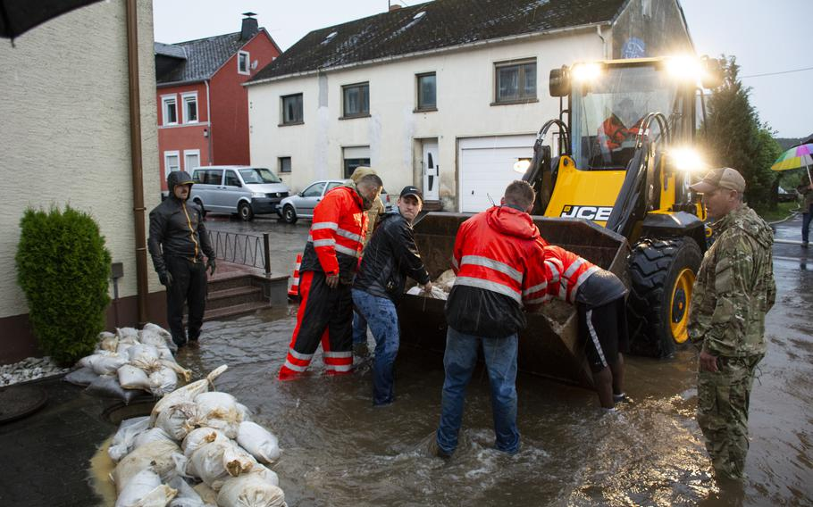 Airmen with the 52nd Civil Engineer Squadron from Spangdahlem Air Base, Germany, work with German first responders and community members to lay sandbags in the town of Binsfeld, Germany, July 14, 2021. About 20 military families at Spangdahlem were displaced by the floods and are being housed in temporary lodging on base.