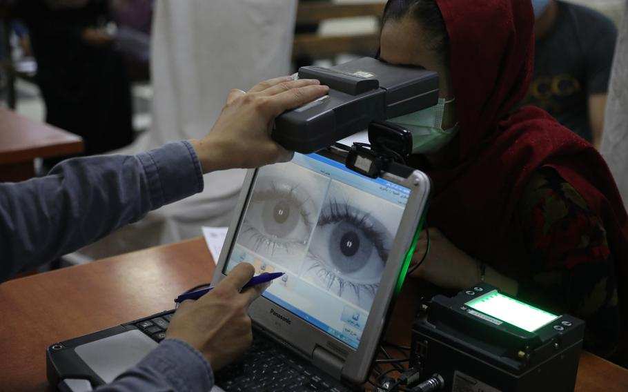 An employee scans the eyes of a woman for biometric data needed to apply for a passport, at the passport office in Kabul, Afghanistan, Wednesday, June 30, 2021. Afghans are lining up by the thousands at the Afghan Passport office to get new passports.