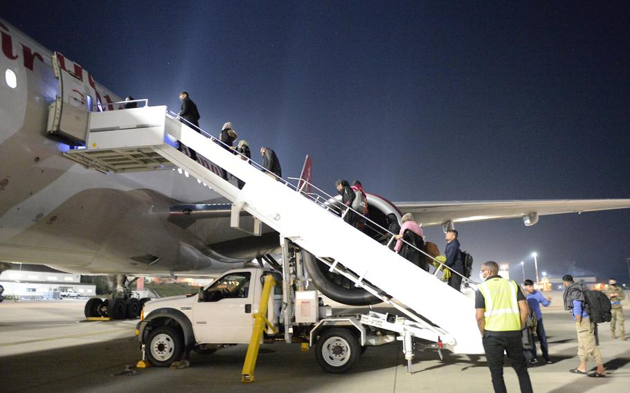 Afghans board an Omni Air International flight to the United States at Ramstein Air Base, Germany, Saturday, Oct. 9, 2021. The flight was the first to leave Ramstein for the U.S. since health officials halted flights three weeks ago, after measles cases were diagnosed in some evacuees.