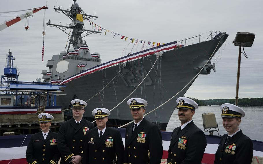 Naval officers pose in front of a warship named for Sen. Carl M. Levin, D-Michigan, Saturday, Oct. 2, 2021, at Bath Iron Works in Bath, Maine. The Arleigh Burke class destroyer was christened on Saturday. (AP Photo/Robert F. Bukaty)