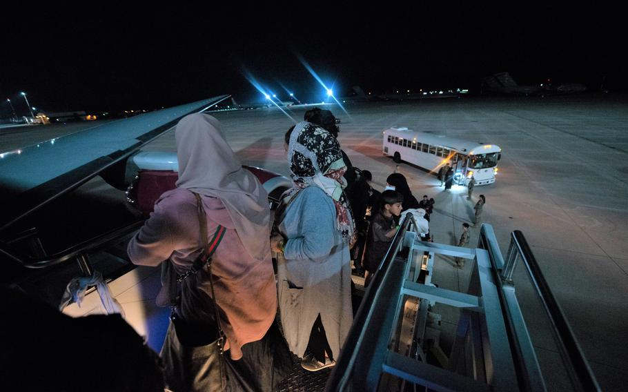 Evacuees board a flight to the U.S. from Ramstein Air Base, Germany, Saturday, Oct. 9, 2021. The flight was the first to leave Ramstein after a three-week pause, imposed by health officials after measles cases were detected in several Afghans after they had arrived in the U.S. from overseas bases.