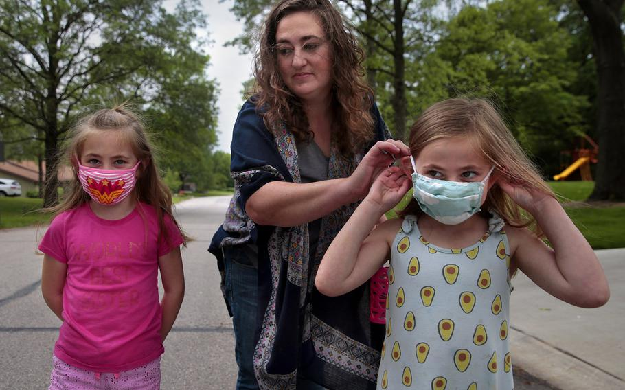 Jenny Berla helps her twins Isla, left, and Elodie with their masks as they approach their sister's school to pick her up after class on Wednesday, May 19, 2021. Berla, who is planning to send the girls to kindergarten this fall, is concerned that dropping mask mandates before young children are eligible for vaccinations leave them open to risk.
