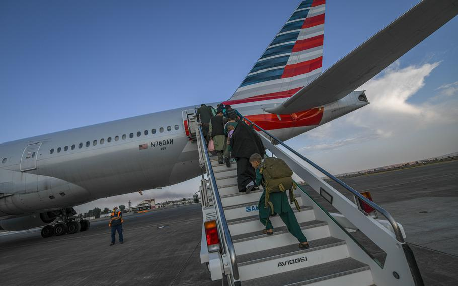 Evacuees from Afghanistan board a Boeing 777 bound for the United States from Naval Air Station Sigonella, Italy, Saturday, Aug. 28, 2021. Two evacuee flights left the air station over the weekend.