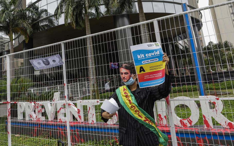"""A demonstrator in a Brazilian President Jair Bolsonaro mask protests against the Prevent Senior health care company outside its headquarters in Sao Paulo, Brazil, Sept. 30, 2021. Whistleblowing doctors, through their lawyer, testified at the Senate last week that Prevent Senior enlisted participants to test unproven drugs without proper consent and forced doctors to toe the line on prescribing unproven drugs touted by Bolsonaro as part of a """"COVID kit,"""" in the treatment of the new coronavirus."""