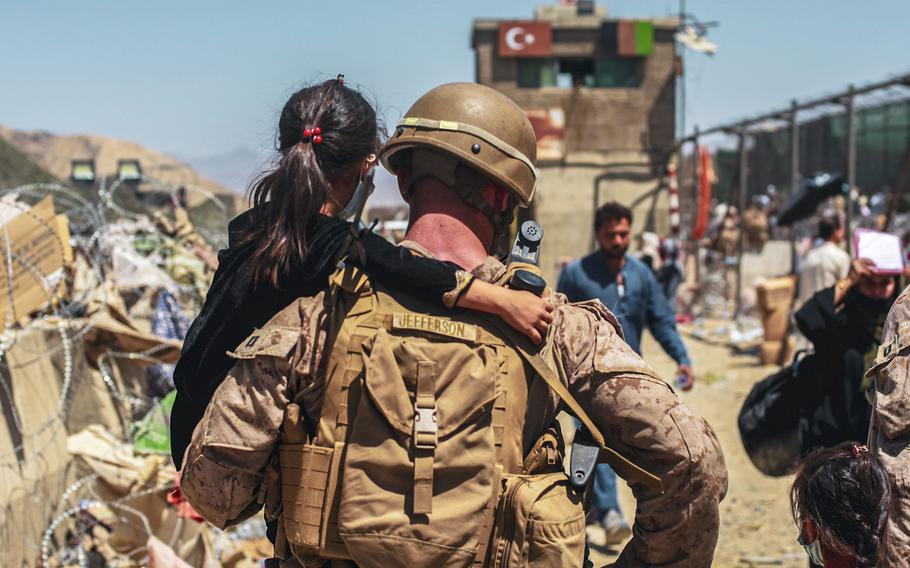 A Marine assigned to the Special Purpose Marine Air Ground Task Force-Crisis Response- Central Command carries a child during an evacuation at Hamid Karzai International Airport, Kabul, Afghanistan, Aug. 25, 2021.