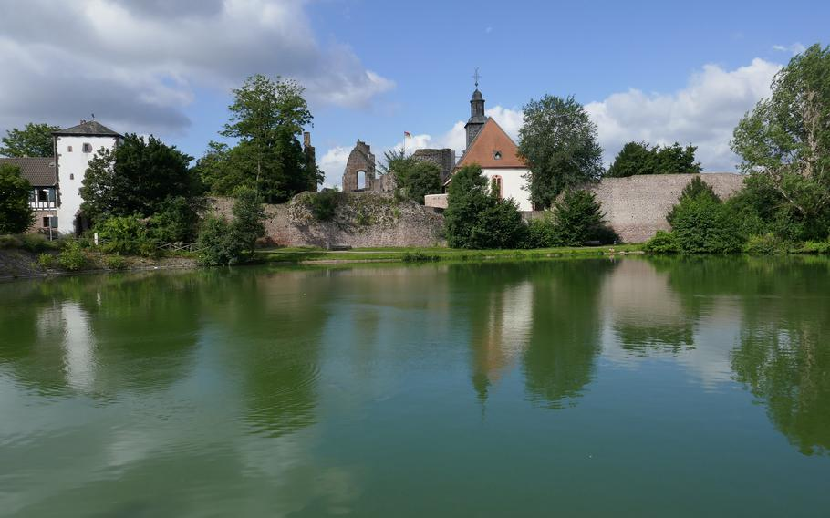 The white Untertor, an old city gate at left, and Burg Hayn, the town's medieval castle, are reflected in a pond in Dreieichenhain, Germany.
